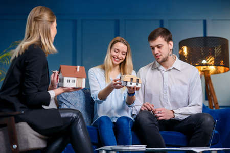 Happy beautiful couple discussing design of house with young female designer in the blue office. Stockfoto