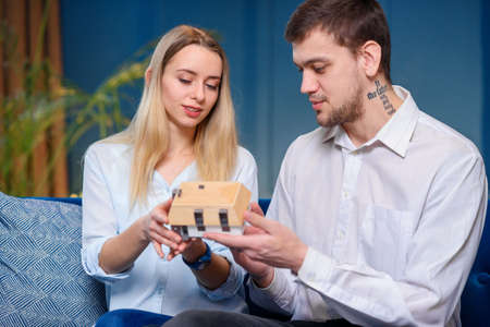 Attractive caucasian man and woman discussing design of the model of 3d maket of house. Stockfoto