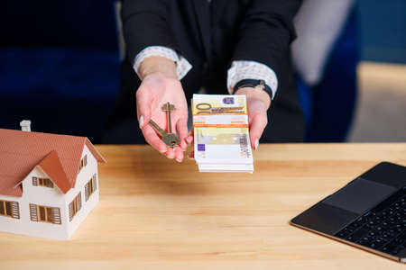 Female realtor hands with key from house and money.