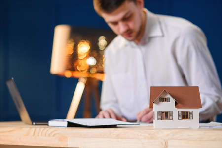 3d model of house on the table with male designer, architect working on the laptop on the background. Stockfoto