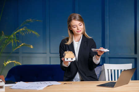 Cute female realtor with money and 3d maket of house in hands on blue wall background