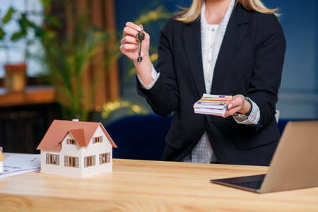 Real estate agent with key from house and money in the hands. Stockfoto