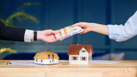 Woman hands giving money for new house, flat to the realtor. Stockfoto