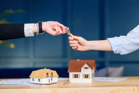 Female clients taking key from female realtor.