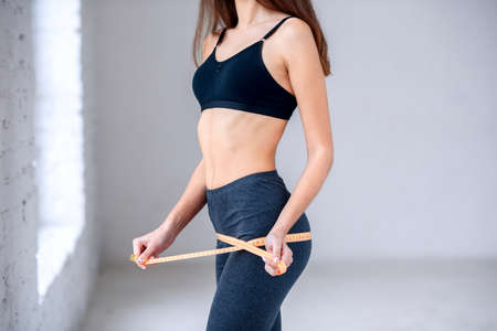 Concept of healthy eating, diet. Young girl with attractive fitness body holding measuring tape in hands.