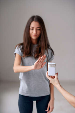 Healthy young beautiful girl refusing to take cigarette from package. Portrait of female showing stop sign with hand to cigarettes. Quit smoking, health care concept.