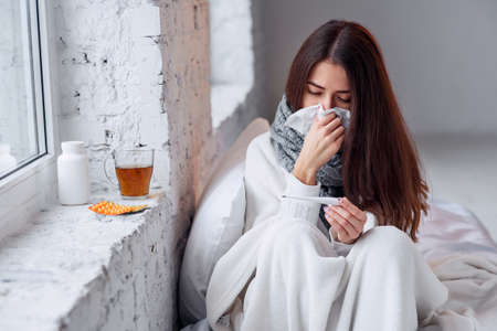 Sick woman caught cold, feeling illness and sneezing in paper wipe. Closeup of beautiful unhealthy girl covered in blanket wiping nose and looking at thermometer. Healthcare concept.