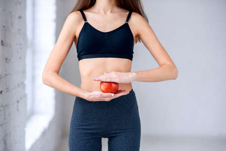 Beautiful slim girl in dark sportwear holding red apple in the hands near her attractive belly. Healthy lifestyle, diet, nutrition, concept. Stock Photo