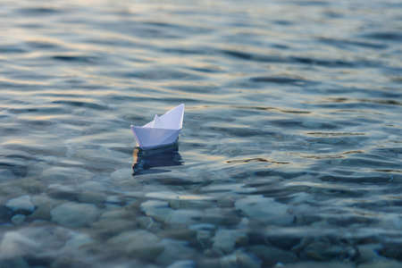 Origami paper boat sails on the surface of water