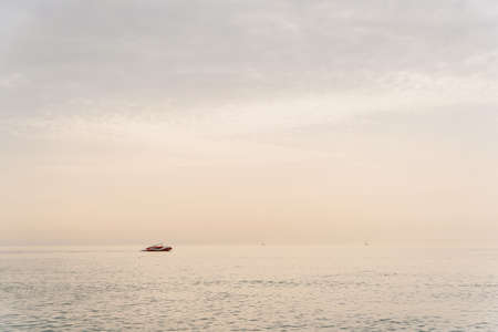 Speed boat floats on the horizon line at sea in the sunrise. Stok Fotoğraf - 126240227