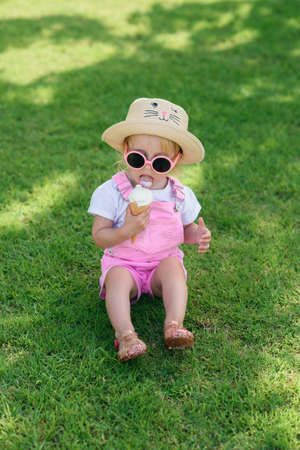 Happy baby girl dressed pink summer clothes, yellow hat and pink sunglasses sits on a green lawn and eats white ice cream in a sunny garden. Stockfoto