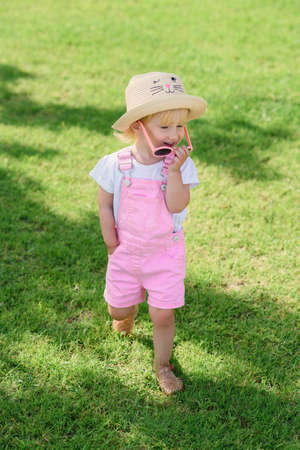 Smiling girl wearing pink sunglasses and walks on green lawn. The concept of summer vacation and carefree childhood.