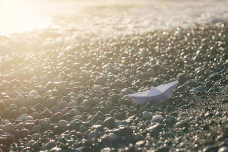 Paper boat lies on the seafront at sunrise. Stockfoto