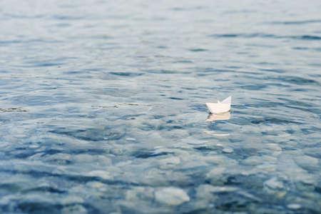 Papierowa łódź origami pływa po powierzchni wody