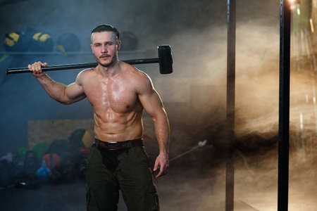 Strong muscular man with hammer on the shoulder.