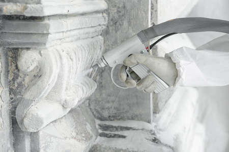 Hand of worker with the gun for serving a high-pressure sand jet. Professional restoration of historical buildind with stone carved decorative elements.