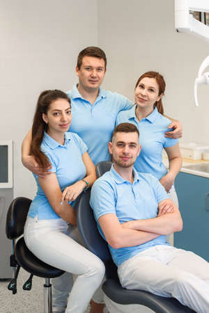 Group of young and happy dental doctors stand near each other at dental clinic. Teamwork and business concept.