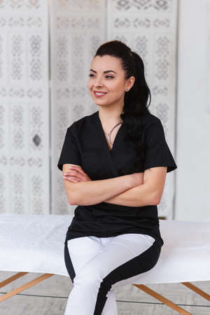Smiling doctor looking at camera and standing behind massage table in modern medical office. Health care and medical concept.