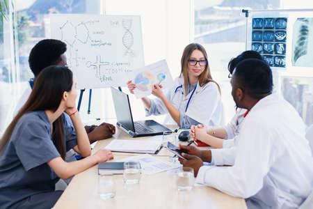 Femme médecin tenant dans les mains le résultat des rayons X lors de la réunion dans une clinique moderne. Des médecins professionnels de plusieurs groupes ethniques examinent les poumons à rayons X du patient. Concept de soins de santé.