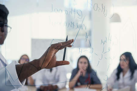 Young multiethnic interns listening lecture afro american doctor at medical conference in the clinic. During lecture the doctor writtig on board some formula for internes in the conference room at Stock Photo