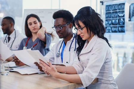 Doctors are studying disease patients history. Team of multiethnic young doctors having a meeting in conference room in the modern bright hospital.