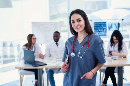 Ärztin in grauer Uniform mit Stethoskop am Hals in medizinischer Kleidung, die in die Kamera lächelt und die Hände kreuzt, während das medizinische Team im modernen Krankenhaus am Hintergrund arbeitet. Standard-Bild
