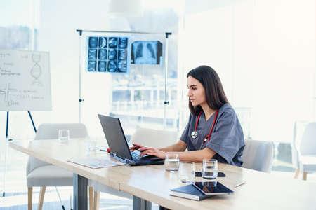 Une jeune femme médecin travaille avec un ordinateur portable dans la salle de conférence de l'hôpital. Un médecin professionnel en uniforme médical examine l'analyse des patients. Banque d'images