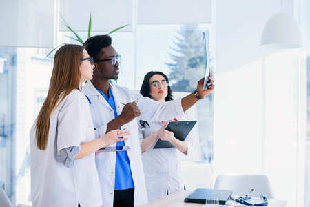 Professional multi ethnic doctors are examining a patients X-ray. Two female doctors and one male doctor work together at one team. Teamwork and medical concept. Stock Photo