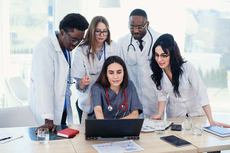 Group of multi national doctors using laptop for discussing analysis in the conference room. Side view.