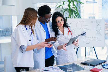 Three professional doctors are examining a patients X-ray. Two women doctors and one male doctor work together as a team. Medical concept.