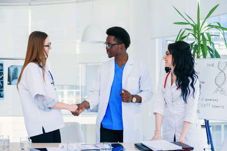 Professional team of one male and two female doctors reached a joint decision to diagnose the patient. Health care and medical concept. Stock Photo
