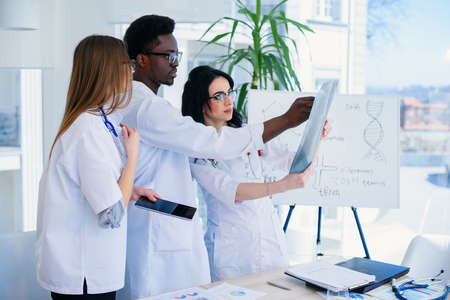 Professional doctors are examining a patients X-ray. Two women doctors and one male doctor work together as a team. Teamwork and medical concept. Stock Photo