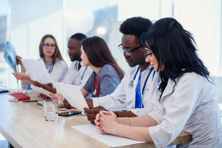 Group of doctors are studying disease patients history. Team of multiethnic young doctors having a meeting in conference room in the modern bright hospital.
