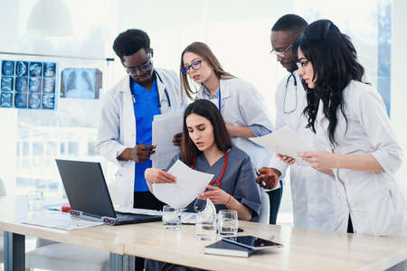 Group of young multi national doctors during working with laptop in the conference room. Stock Photo