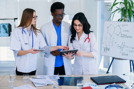 three international doctors discussing lungs xray of the patient on the hospital room background. Healh care concept. Stock Photo
