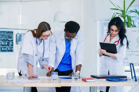 Professional team of doctors discussing patients x-rays results. Multi ethnic group of medical students discuss patients diagnosis. Stock Photo