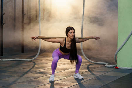 Young woman does barbell squats in modern gym Banco de Imagens