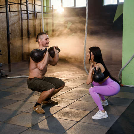 Attractive young couple in sport wear doing exercise in the gym. Banco de Imagens