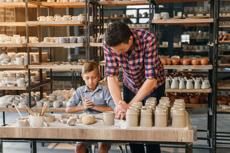 Attractive caucasian man and liitle cute boy kneading clay for pots. Banco de Imagens