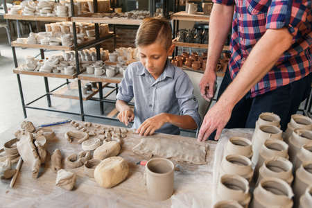 Middle age caucasian father teaching little son how to work with clay on potters wheel.