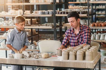 Caring father teaching little son how to work with clay on potters wheel.