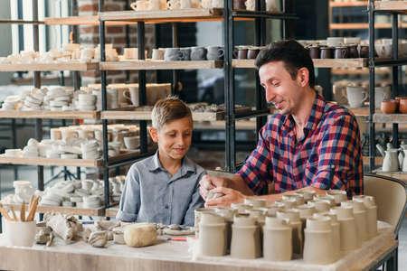Attractive caucasian man and his cute son having fun in pottery. Banco de Imagens