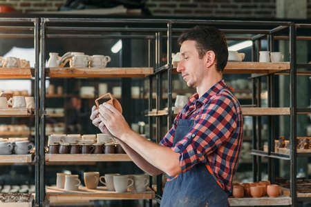 Cute middle age man looking to the handmade cap in the pottery.