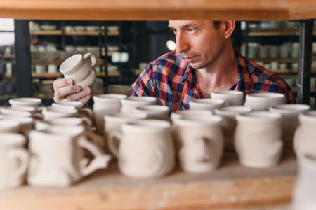 Focused man looking to the handmade cap in the pottery.