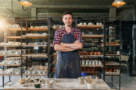 Portrait of happy caucasian creative man as a worker or business owner at the pottery workshop. 写真素材