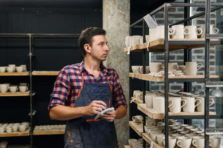 Middle aged male potter in apron notes something in his notebook while counts pottery on shelves. 写真素材