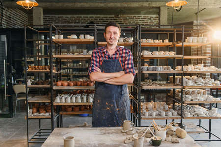 Attractive male potter with crossing hands wearing apron and looking to camera in the pottery workshop with shelves full of ceramics on the background. 写真素材