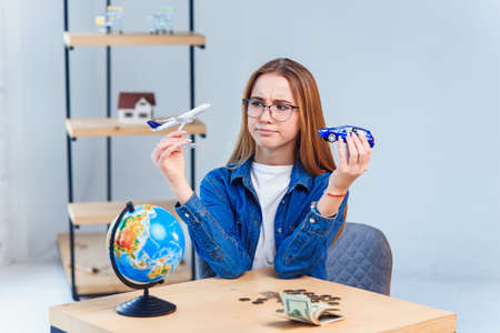 Girl holds airplane and car models in hands and choosing best transportation for trip.Travel around the world for your colorful life. Standard-Bild