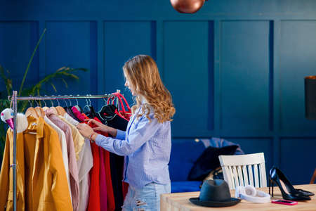 Young attractive smiling woman searching what to wear in a wardrobe Stock Photo