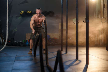 Handsome strong man doing exercises for the muscles with battle ropes in fitness gym.